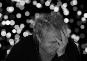 man with Alzheimer's holding face with left hand in despair