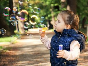 child blowing bubbles in nature