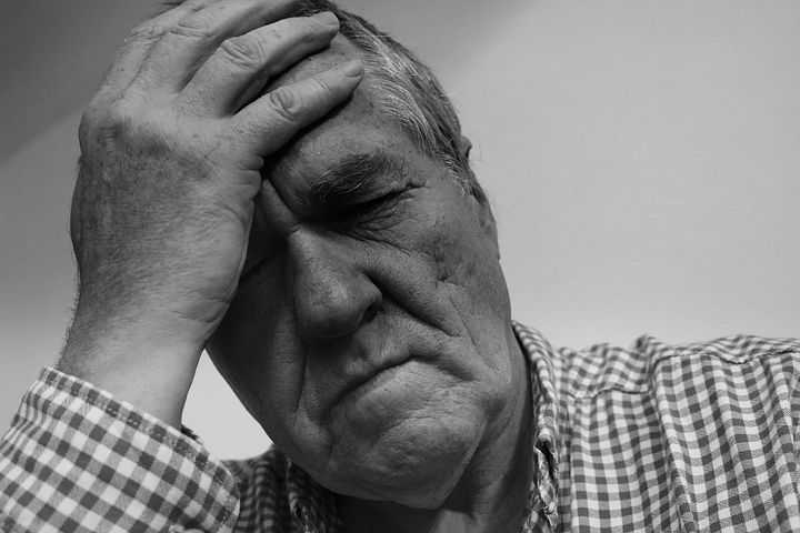 Older man holding head suffering from headache