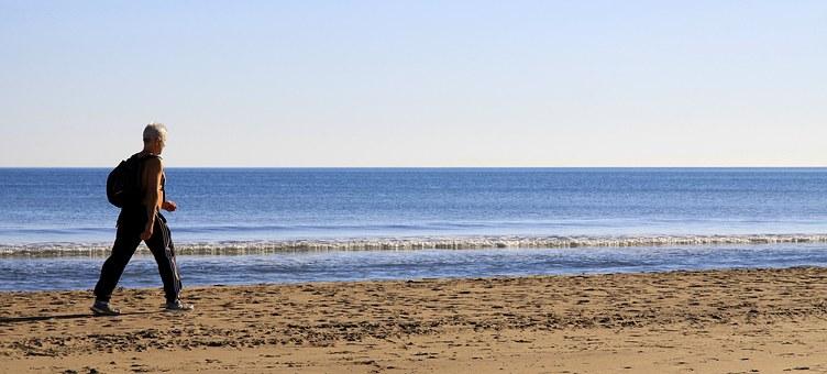 elderly man walking by beach